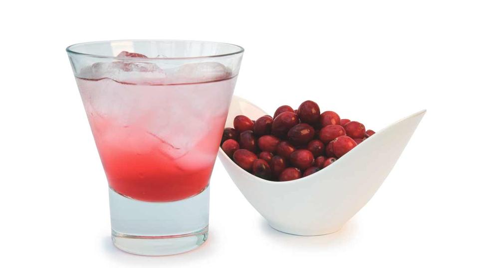 Un pahar cu suc de merișoare lângă un bol cu merișoare.